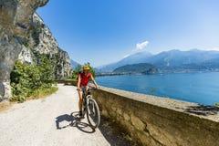 Góra jechać na rowerze przy wschód słońca kobietą nad Jeziornym Gardą na ścieżce Sentier obrazy royalty free