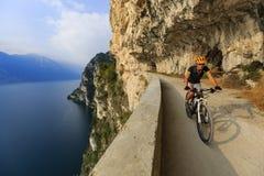 Góra jechać na rowerze przy wschód słońca kobietą nad Jeziornym Gardą na ścieżce Sentier obraz royalty free