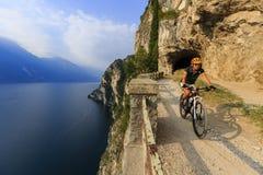 Góra jechać na rowerze przy wschód słońca kobietą nad Jeziornym Gardą na ścieżce Sentier fotografia stock