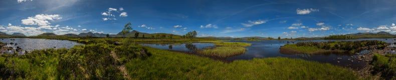Góra krajobraz w Glencoe terenie w Szkocja, wiosna widoku góry z obszarem trawiastym i wsi drogą w dolinie Obraz Stock