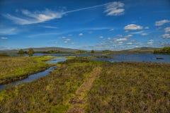Góra krajobraz w Glencoe terenie w Szkocja, wiosna widoku góry z obszarem trawiastym i wsi drogą w dolinie Zdjęcie Royalty Free