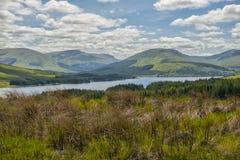 Góra krajobraz w Glencoe terenie w Szkocja, wiosna widoku góry z obszarem trawiastym i wsi drogą w dolinie Zdjęcia Royalty Free