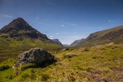 Góra krajobraz w Glencoe terenie w Szkocja, wiosna widoku góry z obszarem trawiastym i wsi drogą w dolinie Zdjęcia Stock