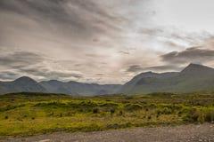 Góra krajobraz w Glencoe terenie w Szkocja, wiosna widoku góry z obszarem trawiastym i wsi drogą w dolinie Obraz Royalty Free