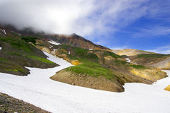 Góra krajobraz z zieloną trawą i śnieżnymi ziemiami Zdjęcia Stock