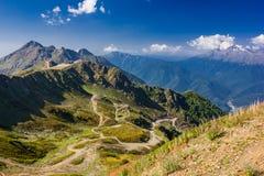 Góra krajobrazowy jasny dzień z skałami, wężowata droga, niebieskie niebo Obrazy Royalty Free