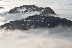 Góra nakrywa przebijanie przez gęstej warstwy chmury Fotografia Stock