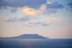 Góra w morzu przy zmierzchem Fotografia Stock