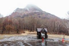 Góra z śniegiem i mgła na wierzchołku, drzewach i strażowym domu below przy carpark Noboribetsu niedźwiedzia park w hokkaidu, Jap zdjęcia royalty free