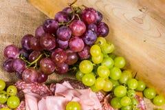 Górny widok salami, mortadella, kolor żółty i czerwony muszkatołowy winogrono na, drewnianej desce kanwie i Fotografia Stock