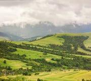 Górska wioska na zielonym wzgórzu pod ciężkimi dżdżystymi chmurami Obrazy Royalty Free