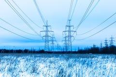 Góruje elektryczna magistrala w zimy wsi polu na tle niebieskie niebo i lesie z drutami obrazy royalty free