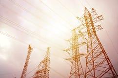 Góruje linie energetyczne przeciw chmurnego nieba tłu elektryczność zdjęcie royalty free