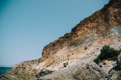 Góry i błękitny morze z skałami Zdjęcia Royalty Free