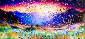 Góry i pole kwiatów A widok miasto od okno od wysokiego punktu podczas deszczu Ostrość na kroplach Fotografia Stock