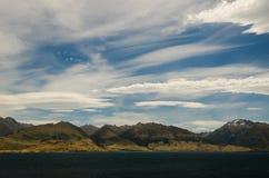 Góry kształtują teren z jeziorem w przodzie na błękitny clo Zdjęcie Royalty Free