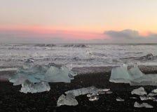 Góry lodowa na czarnym piasku wyrzucać na brzeg pod pięknym różowym zmierzchu niebem, Iceland Obraz Stock