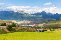 Góry, wioski, kościół, paśniki zakrywający białymi chmurami, Qilian góry w Qinghai obrazy royalty free