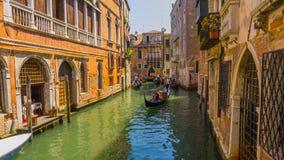 Gôndola com turistas, canal e as casas velhas na arquitetura tradicional do distrito histórico de Veneza imagens de stock royalty free