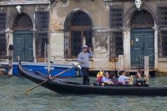 Gôndola Venetian do enfileiramento do gondoleiro com os turistas através de Grand Canal, Veneza, Itália Foto de Stock