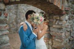 Gömd kyss av bruden och brudgummen royaltyfri foto
