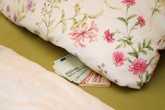 Gömda pengar i säng under kudden arkivbilder