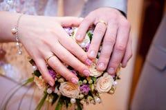 Gömma i handflatan av bruden och brudgummen på buketten Royaltyfri Bild