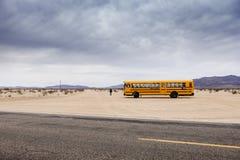 29 gömma i handflatan, California/USA-03/21/2016: Skolbuss i öknen, 29 gömma i handflatan, pojken går in mot horisonten Arkivbilder