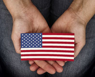 Gömma i handflatan den hållande amerikanska flaggan för kvinnan på henne Royaltyfria Foton