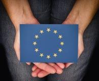 Gömma i handflatan den hållande europeiska flaggan för kvinnan på henne Arkivbild