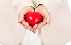 Gömma i handflatan den hållande hjärtamodellen för den äldre kvinnan på öppet Fotografering för Bildbyråer