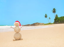 Gömma i handflatan den sandiga snögubben för jul i den santa hatten på havstranden Royaltyfri Bild