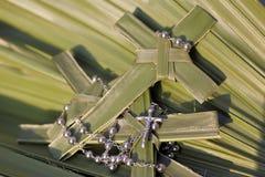 Gömma i handflatan kors och radbandpärlor på palmblad royaltyfri fotografi