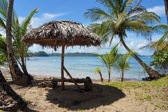 Tropisk strand med det thatched paraplyet Royaltyfri Fotografi