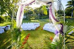 Gömma i handflatan-satt fransar på bröllopbåge i frodig tropisk trädgård med flamboyanta träd fotografering för bildbyråer