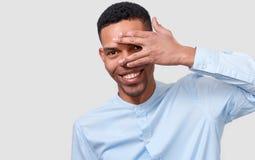 Gömma i handflatan visar den stiliga unga mannen för afrikanska amerikanen som döljer hans framsida med, och hans öga arkivbild