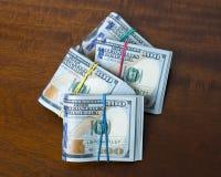 Gömställen av hundra dollarräkningar på trätabellen Royaltyfri Fotografi