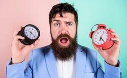 Gör ändrande klockaröra med din hälsa För hipsterhåll två för man skäggiga olika klockor Orakad förbryllad framsida för grabb royaltyfria foton