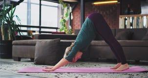 Gör övande yoga för attraktiv blond kvinna månekrigaren som duvan poserar i morgonen hemma i en modern vinddesign arkivfilmer