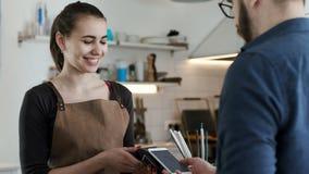 Gör bankbetalning vid telefonen i kaffehus arkivfilmer