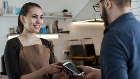 Gör bankbetalning vid telefonen i kaffehus stock video