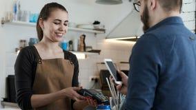 Gör bankbetalning vid telefonen i kaffehus lager videofilmer