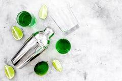 Gör coctailen med absint Shaker skott, limefruktskivor på grått utrymme för bästa sikt för bakgrund för text Royaltyfria Bilder