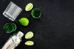 Gör coctailen med absint Shaker skott, limefruktskivor på svart utrymme för bästa sikt för bakgrund för text Royaltyfri Bild