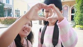 gör den asiatiska visninghanden för lilla flickan 4K och moderhjärta att forma med lycka i semesterlopp stock video