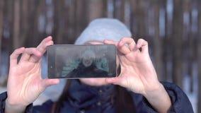 Gör den caucasian flickan för den unga brunetten selfie i en skog som vänder runt om att le i ett mörker - det blåa omslaget och  arkivfilmer