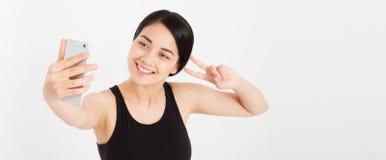 Gör den gulliga flickan för det moderna leendet tecknet för selfie- och för show två fingerfred arkivfoto