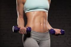Gör den kvinnliga kvinnan för kondition med den muskulösa kroppen, hennes genomkörare Royaltyfri Fotografi