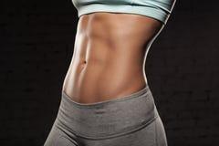 Gör den kvinnliga kvinnan för kondition med den muskulösa kroppen, hennes genomkörare, abs, abdominals Royaltyfria Bilder