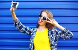 Gör den nätta kvinnan för mode i färgrik kläder som har gyckel, självporträttet på smartphonen arkivbilder